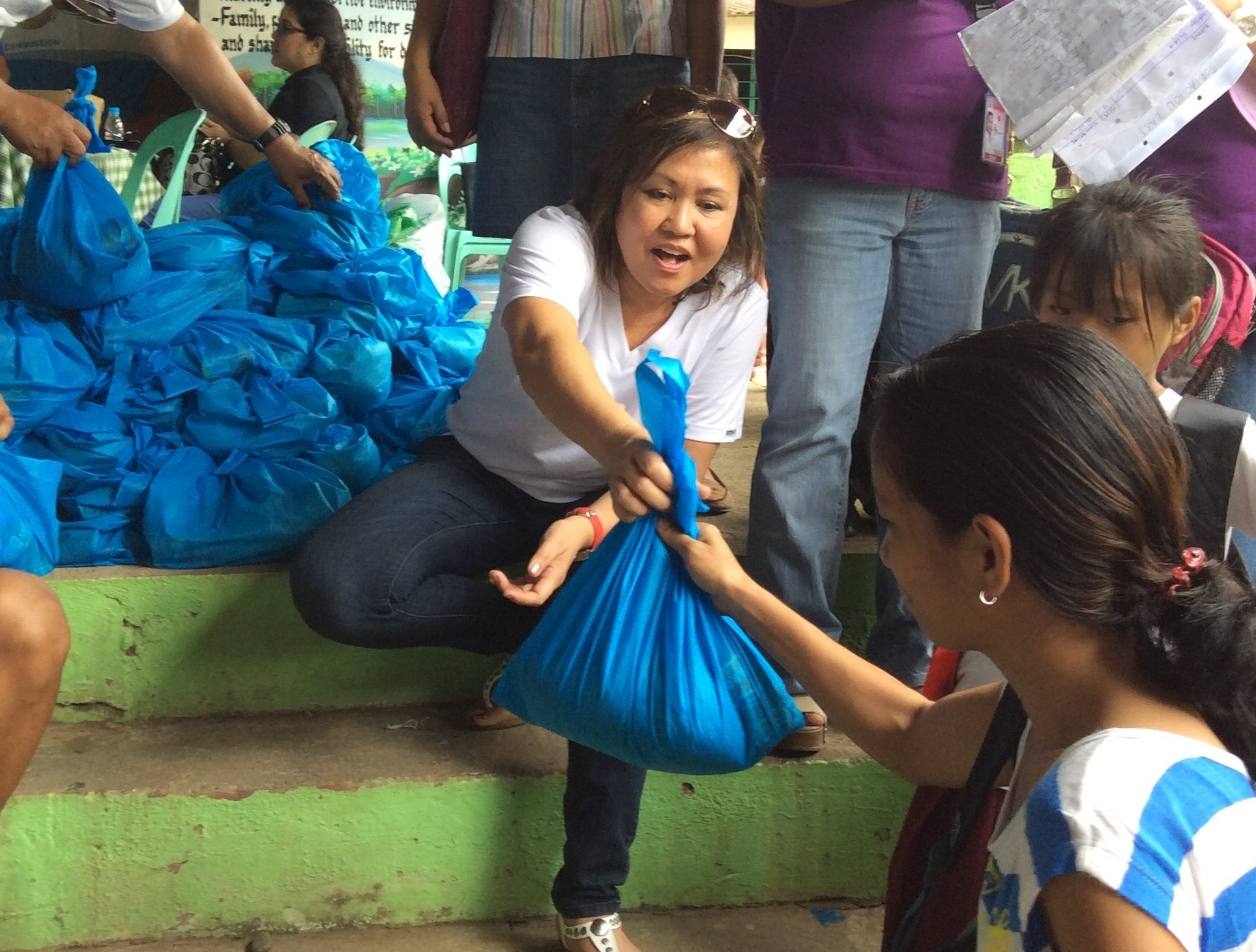 Distributing bags of assorted foods to families in Pugo.